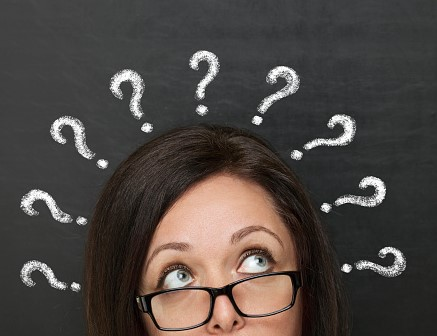 Chalk question marks above woman at blackboard