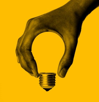 Light bulb in human hand, yellow background.