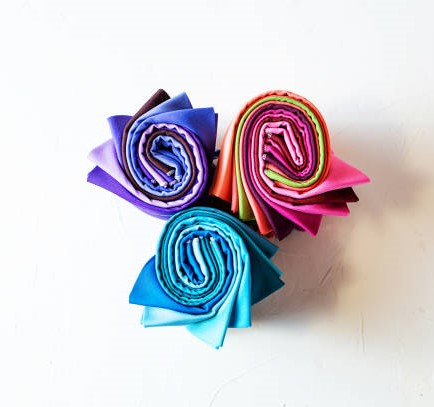 Colorful fabric swatches rolled up on white background.