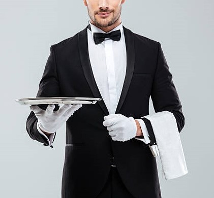 Closeup of young waiter in tuxedo holding metal empty tray and napkin