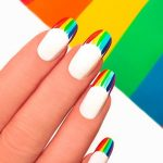French manicure with bright colored stripes on the background.