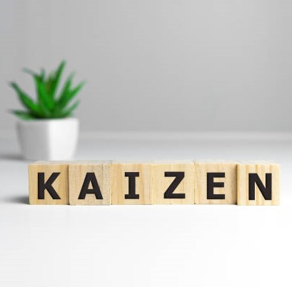 Kaizen improvement sign made of blocks on a wooden desk in a bright room.